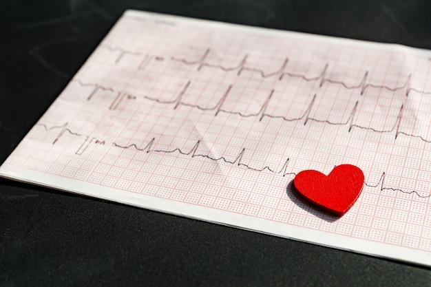 Закройте вверх электрокардиограммы в бумажной форме с красным деревянным сердцем. экг или экг на черном фоне. концепция медицины и здравоохранения.