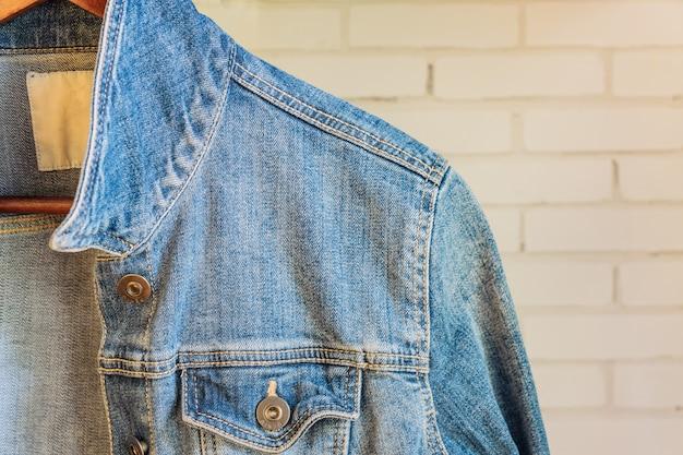 木製ハンガーに青いデニムの女性ジャケット。流行りの服。