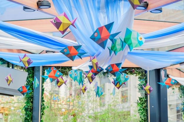 カラフルな紙の魚がぶら下がっています。屋外のお祝いのお祭りのためのペンダント装飾
