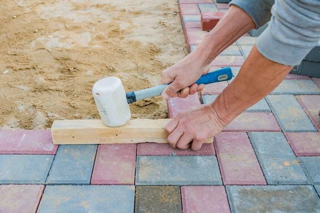 Работник кладя красные и серые бетонные блоки мощения.