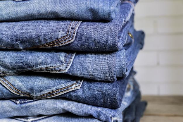 Стог голубых джинсов на деревянной полке. концепция красоты и модной одежды