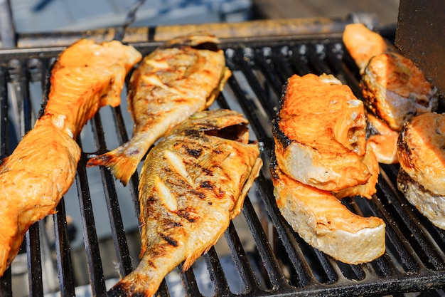 おいしいローストサーモンと屋外グリルのとまり木のクローズアップ。屋台の食べ物。