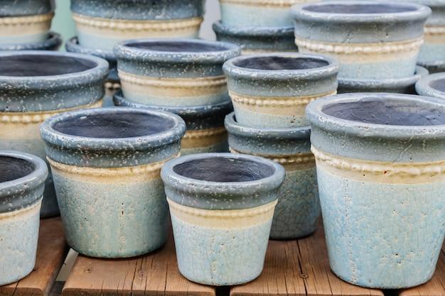 販売のためのたくさんの空の粘土の植木鉢のクローズアップ。庭および室内装飾。