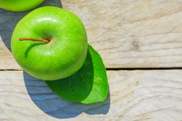 木製のテーブルに新鮮なトリミングされた緑のリンゴ