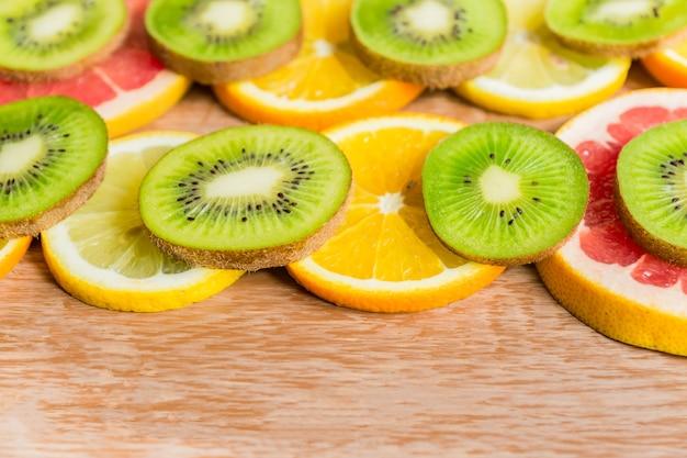 Рамка с ломтиками апельсинов, лимонов, киви, грейпфрута на деревянный стол