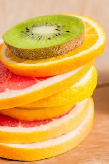Стек ломтик апельсинов, лимонов, киви, грейпфрута на деревянный