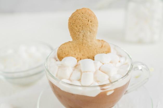 Чашка горячего вкусного какао-напитка с маршмеллоу и имбирным человечком.