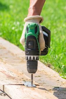 男性の電動ドライバーは、繊維手袋を屋外で手します。裏庭の手のひらツールで作業する人。