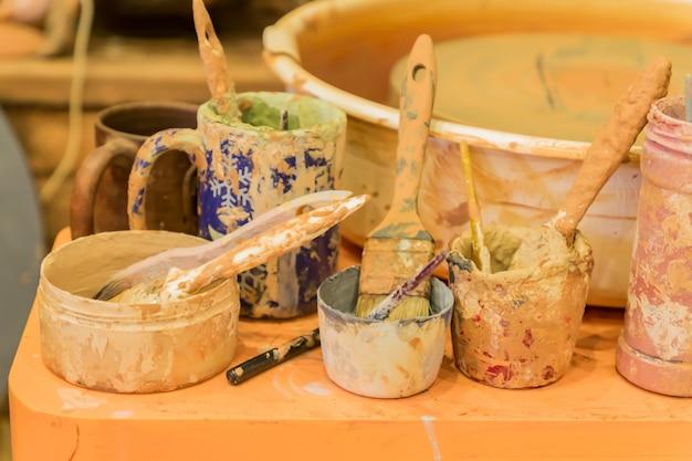 汚れた陶器のホイールと作業後の瓶の中のカラフルな泥のクローズアップ