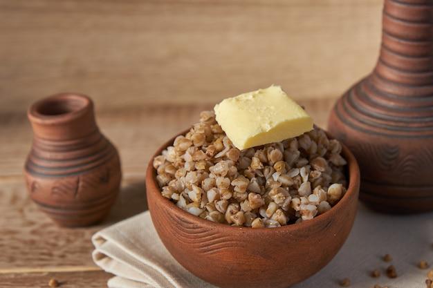 Сваренные хлопья гречихи в шаре коричневой глины на деревянном столе. зерно без глютена для здорового питания