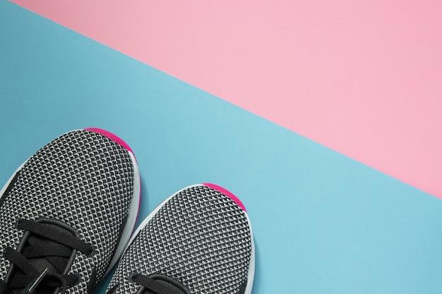マルチカラーの表面にある一対のスポーツシューズ。コピースペースでピンクとブルーのパステル調の背景に新しい黒と白の女性スニーカー。平面図、平置き