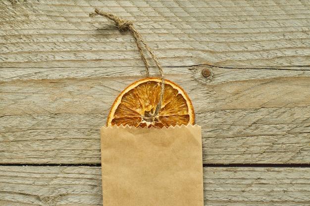 クリスマスの装飾。クラフトペーパーパッケージ、平面図、最小限のフラットレイアウトで乾燥したオレンジスライス