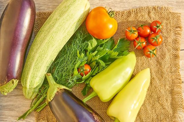 木製テーブルの上の有機野菜の平面図です。健康食品の背景、コピースペース