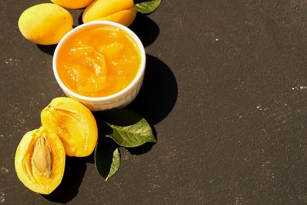 Домашнее органическое абрикосовое варенье в белый шар и спелых абрикосов на черном фоне. жесткий свет