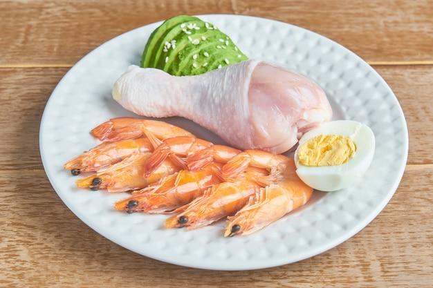プレート上の良い脂肪源-鶏肉、魚介類、卵、アボカド、ゴマ。健康的な食事とケトン食療法のコンセプト