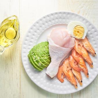 ケトジェニック食品-鶏肉、エビ、卵、アボカド、エキストラオリーブオイルの平面図。健康食品のコンセプト