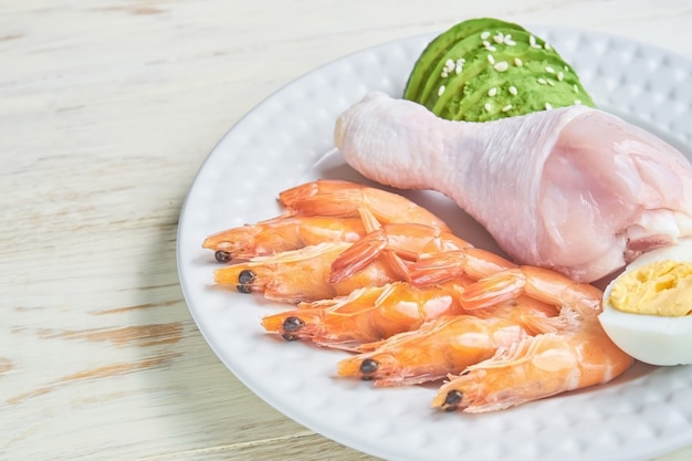 プレート上のケトジェニック低炭水化物ダイエットのコンセプト。エビ、アボカド、卵、ゴマを使った健康的な食事とダイエット。