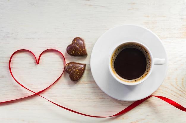 Концепция дня валентинки с кофейной чашкой, шоколадом формы сердца и красной лентой на деревянной предпосылке. вид сверху сверху. плоская планировка