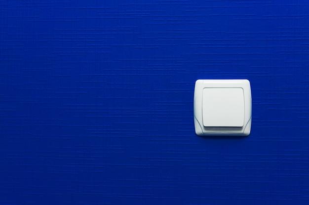 水色の壁の背景の光スイッチ。インテリア・デザイン。最小限のスタイル。