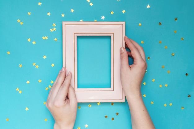 散乱の金の星と青い壁にピンクのフォトフレームを持っている女性の手。クリエイティブモックアップ。