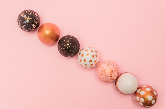 行のカラフルなイースターエッグとピンクの背景は、金、白、黒の色で描かれています。