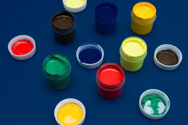 Закройте вверх открытых банок акрила. разноцветные краски на синем фоне