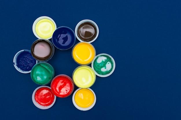 Вид сверху открытых акриловых банок с краской. красочные краски на синем фоне с копией пространства
