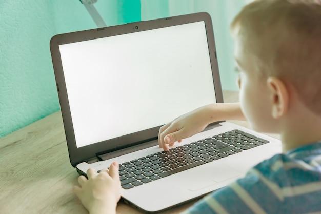 オンライン教育の遠隔学習。ラップトップで自宅で勉強し、学校の宿題をしている少年。