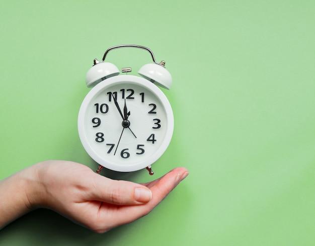 パステルグリーンの背景に目覚まし時計を持っている女性の手。