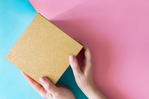 青とピンクの背景の色にゴールドの輝くギフトボックスを保持している女性。お祝いグリーティングカード。休日のコンセプト