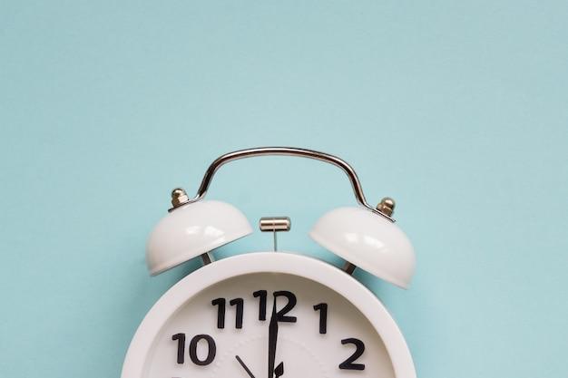 青い背景に白い目覚まし時計。テキストのコピースペースでクローズアップ。