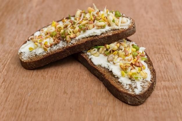 ライ麦パンのサンドイッチとクリームチーズ、緑豆の発芽、クルミ、ヒマワリ、亜麻の木製の壁のクローズアップ。ビーガン、ローフードダイエット。