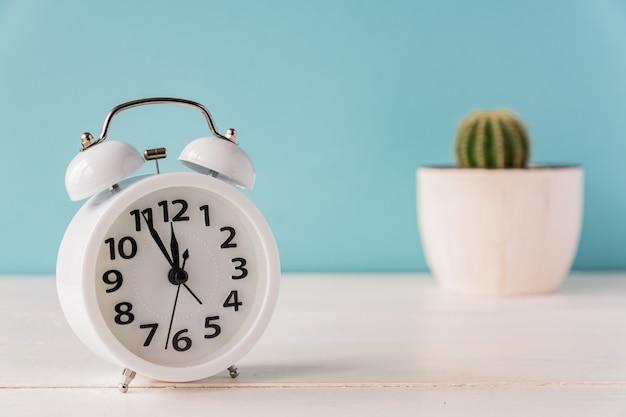 緑の背景に木製の棚の上に立っている白い目覚まし時計。壁に鍋にサボテン。