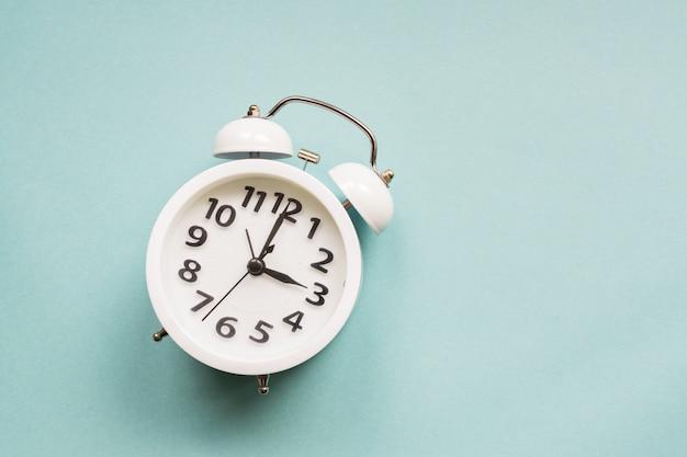 平らな青い色の壁に白い美しい新しい目覚まし時計を置きます。コピースペース付き。