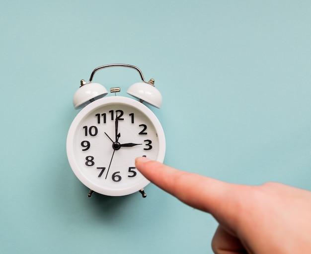 白い目覚まし時計を指している女性の手。締め切りとビジネスコンセプト