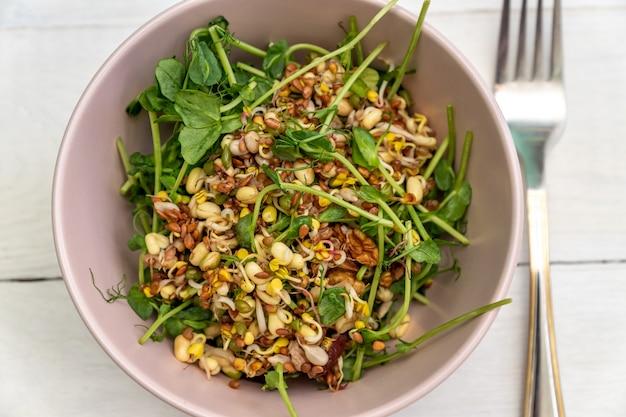 Веганский полезный салат из гороха с зелеными ростками и проросшей фасолью в розовой миске