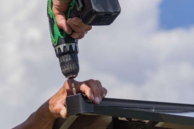 男性の手で電動ドライバー。金属製の構造を組み立てるハンドツールを持つ労働者