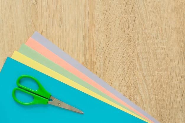 木製のテーブルに色とりどりの紙とはさみのトップビュー