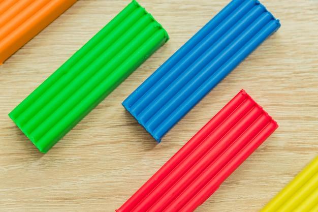 Набор разноцветных пластилиновых батончиков для моделирования на деревянный стол. вид сверху, концепция образования и творчества
