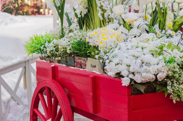咲く人工花でいっぱいの木箱と赤い木製手押し車。
