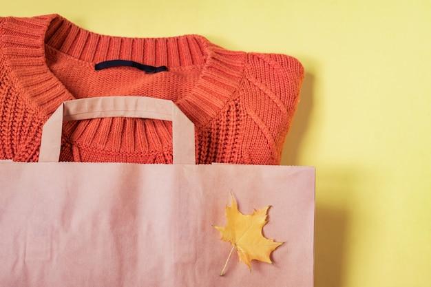 黄色のペーパークラフトパッケージでオレンジ色の女性暖かいセーター