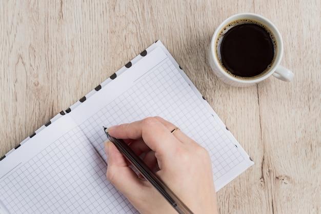 若い女性の手を保持する木製のテーブルの上のコーヒーカップの横にある黒いペンで開いているノートページ。上面図。
