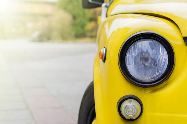 丸いヘッドライトと黄色のレトロな車のクローズアップ。