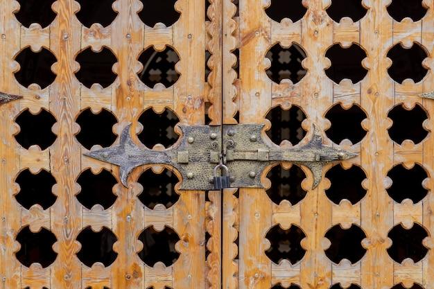 ロックされた彫刻が施された木製の門を閉じる
