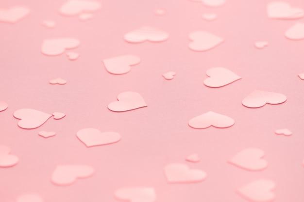 バレンタインデーのピンクのハートの紙吹雪とピンクの背景