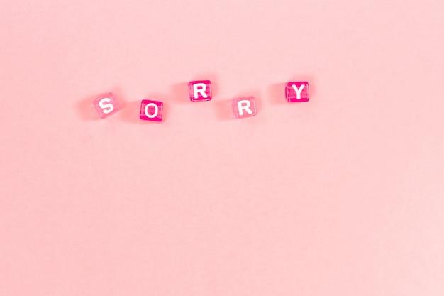 カラフルなキューブビーズの文字で作られた申し訳ありませんが碑文。コピースペースとお祝いのピンクの背景の概念