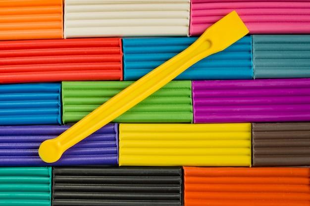 Радужные цвета лепки из глины. разноцветный пластилин баров фон с желтой пластиковой палочкой.