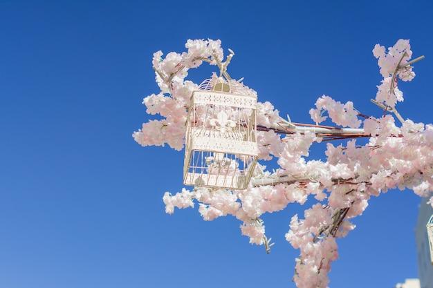 空を背景に咲くリンゴの木の枝にぶら下がっている白い装飾的な鳥かご。春の街の装飾