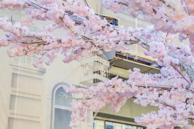 背景の建物に咲くリンゴの木の枝にぶら下がっている白い装飾的な鳥籠。春の街の装飾