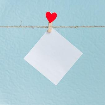 赤いハートのピンの空白カード。バレンタインデーの挨拶のテキストと青色の背景のモックアップ